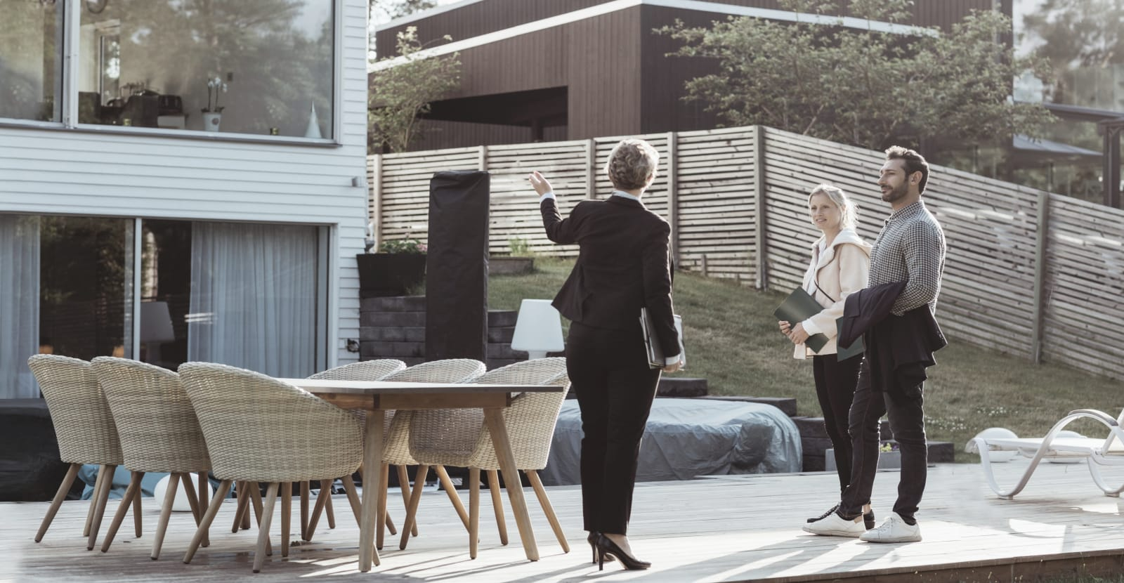 A real estate agent in a suit is standing with a couple on a patio outside a house.