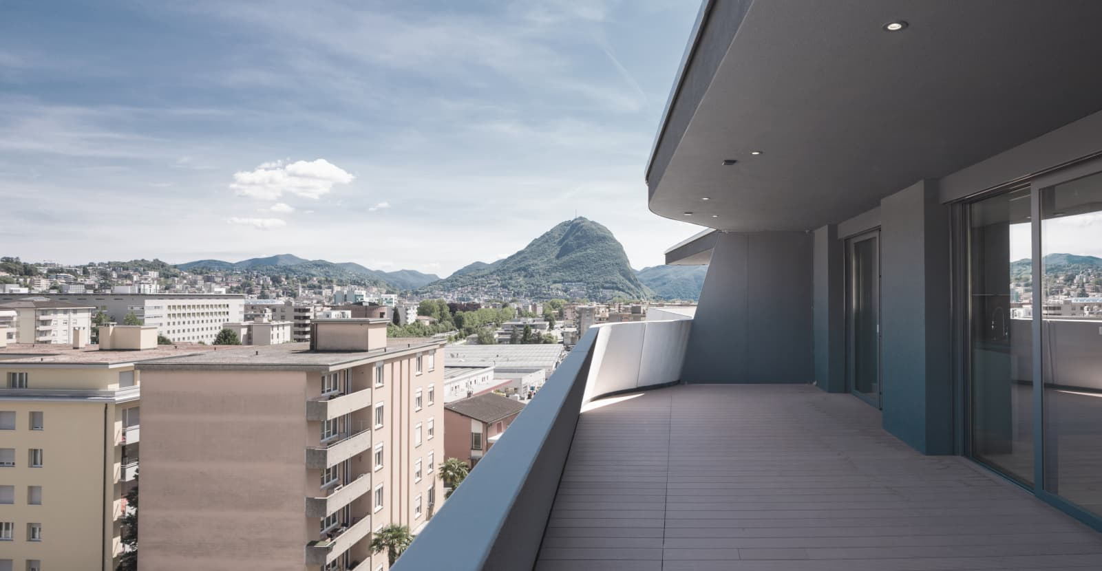 From the terrace of a tall building, you can see the rooftops of Lugano, with Monte San Salvatore in the background.