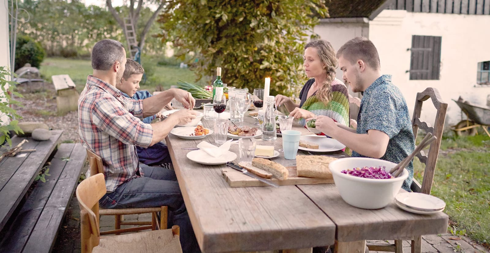 A family sits and eats at a large table in the garden in front of a house.