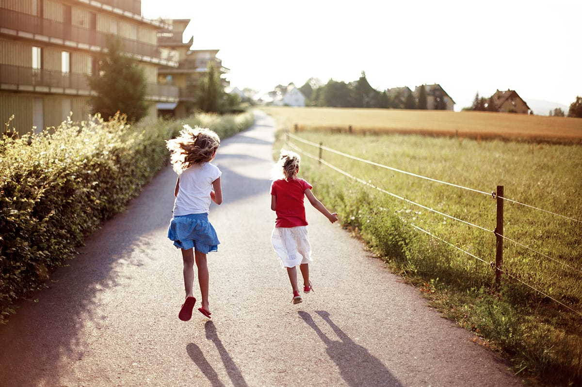 Two children run along a path in rural surroundings.