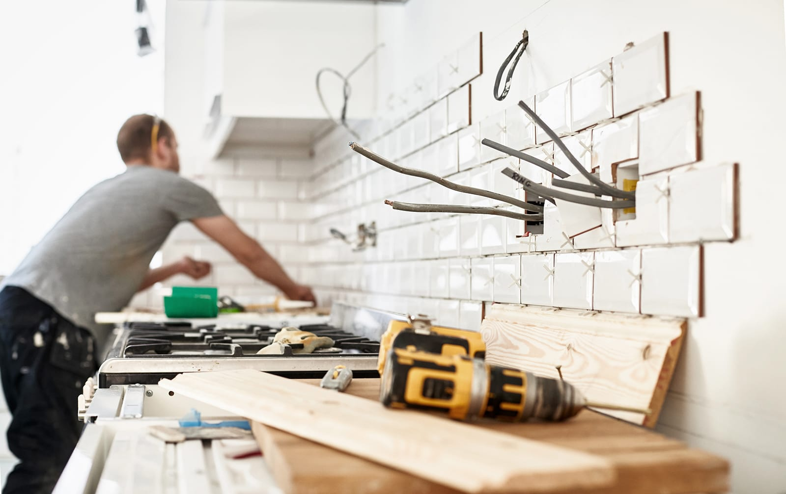 A craftsman is working in a kitchen, a drill lies on some wood in the foreground.