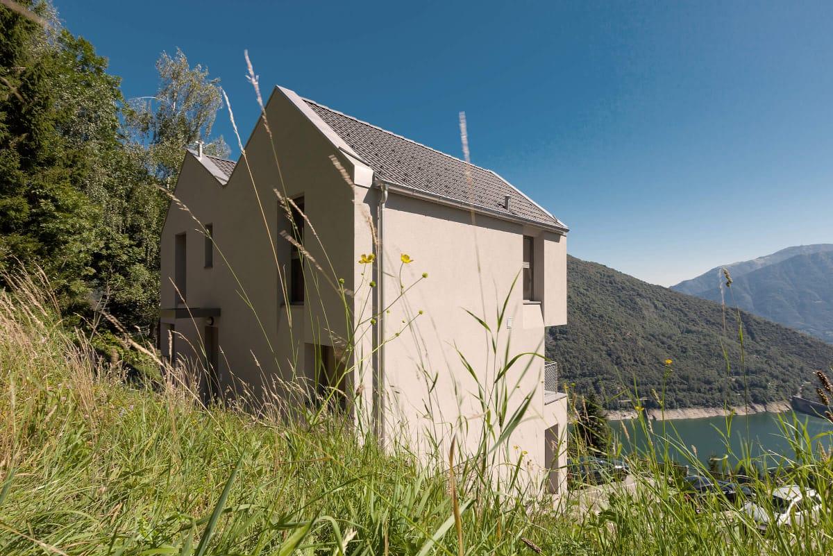 Une maison jumelle au bord d'un lac; à l'avant-plan, une prairie dessine la bordure de l'image.