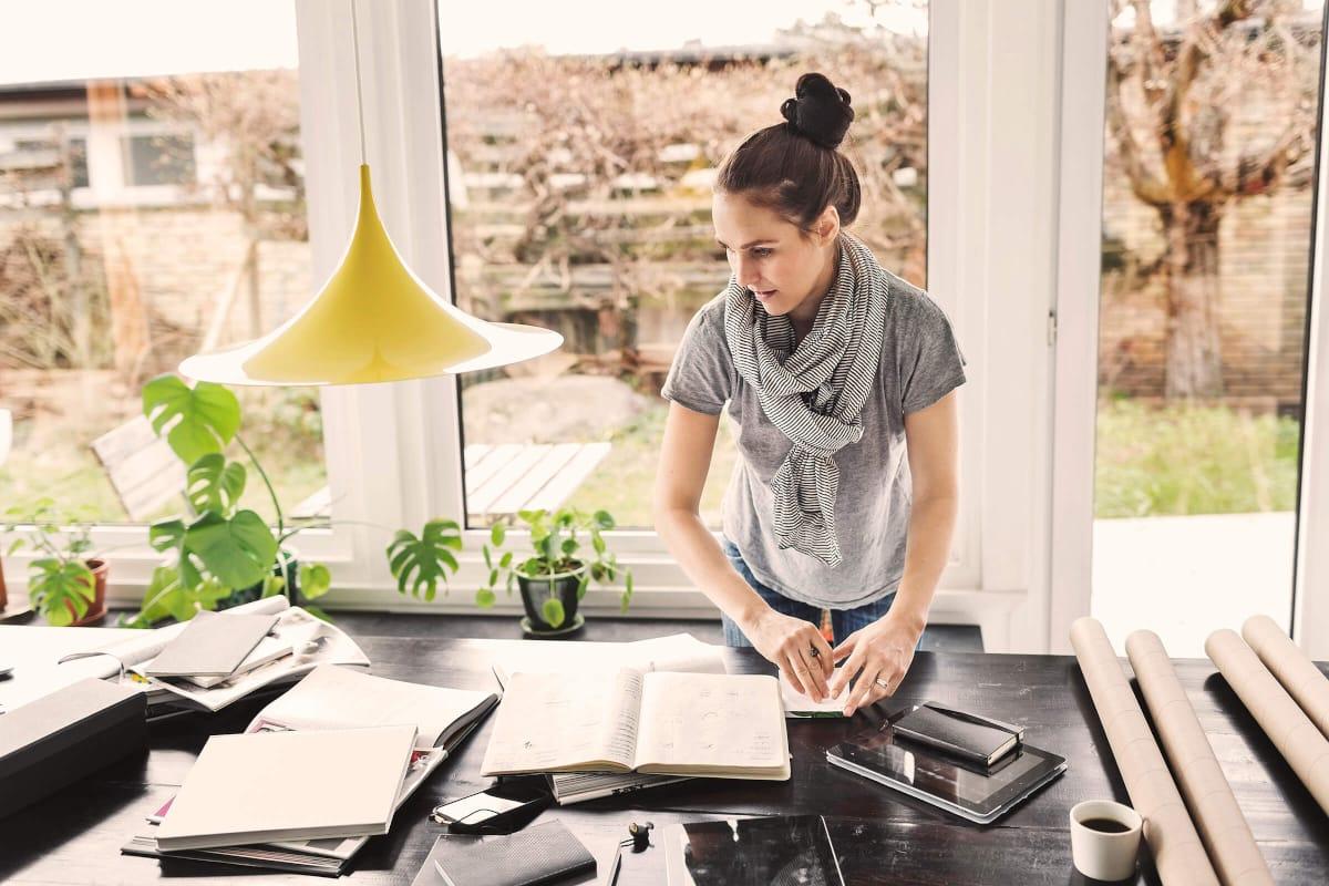 Une femme se tient debout à un grand bureau, devant elle, divers carnets, sur l'appui de fenêtre de la grande baie vitrée, on peut voir plusieurs plantes vertes.