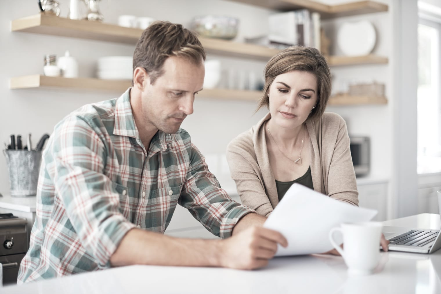 A man and a woman are concentrating on documents that the man is holding in his hands; kitchen shelves are visible in the background.