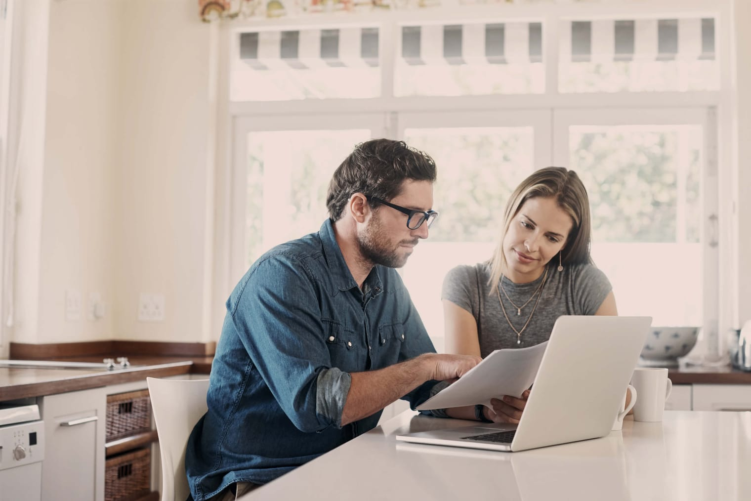 A man and a woman are sitting at a laptop in their kitchen.