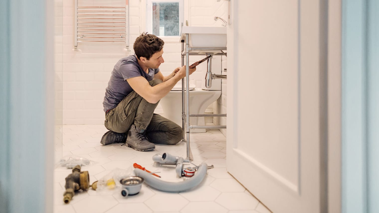 A man kneels in front of a washbasin in the bathroom and screws in a replacement drain system.