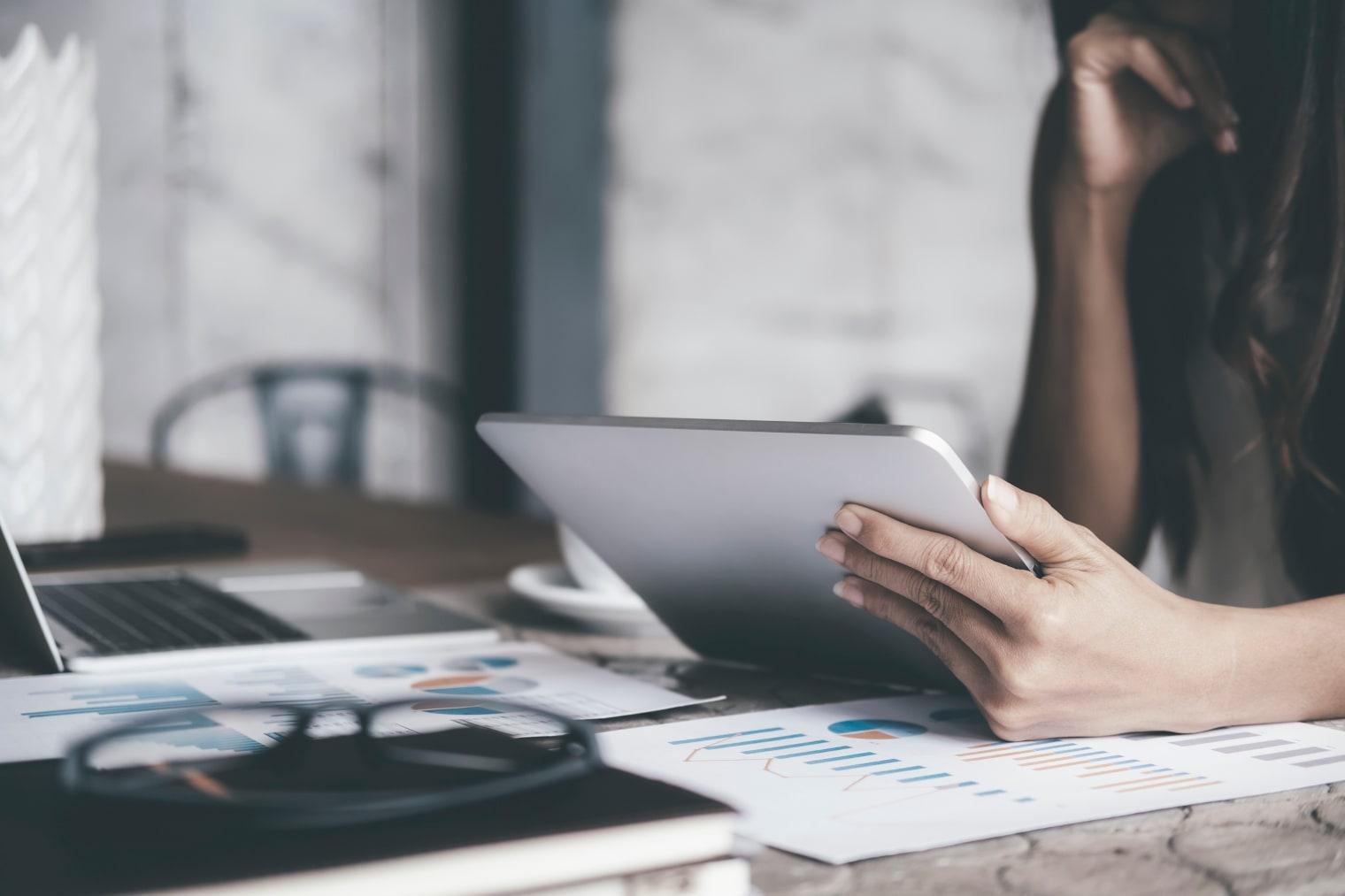 Une femme est assise à un bureau et regarde attentivement une tablette; sur le bureau se trouvent des papiers avec des diagrammes et un ordinateur portable.