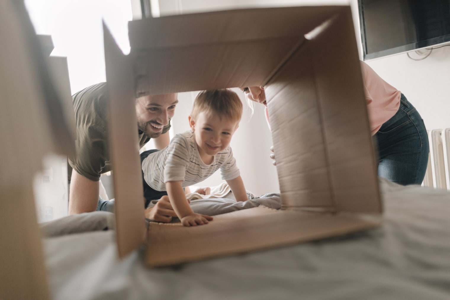 A toddler is smiling as he crawls through a tunnel made out of a cardboard box. A man and a woman, also smiling, can be seen behind him.