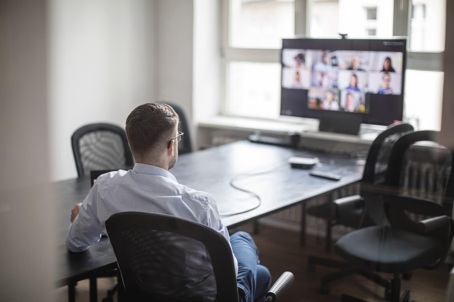 In una sala conferenze, un dipendente siede davanti a uno schermo e partecipa a una videoconferenza.