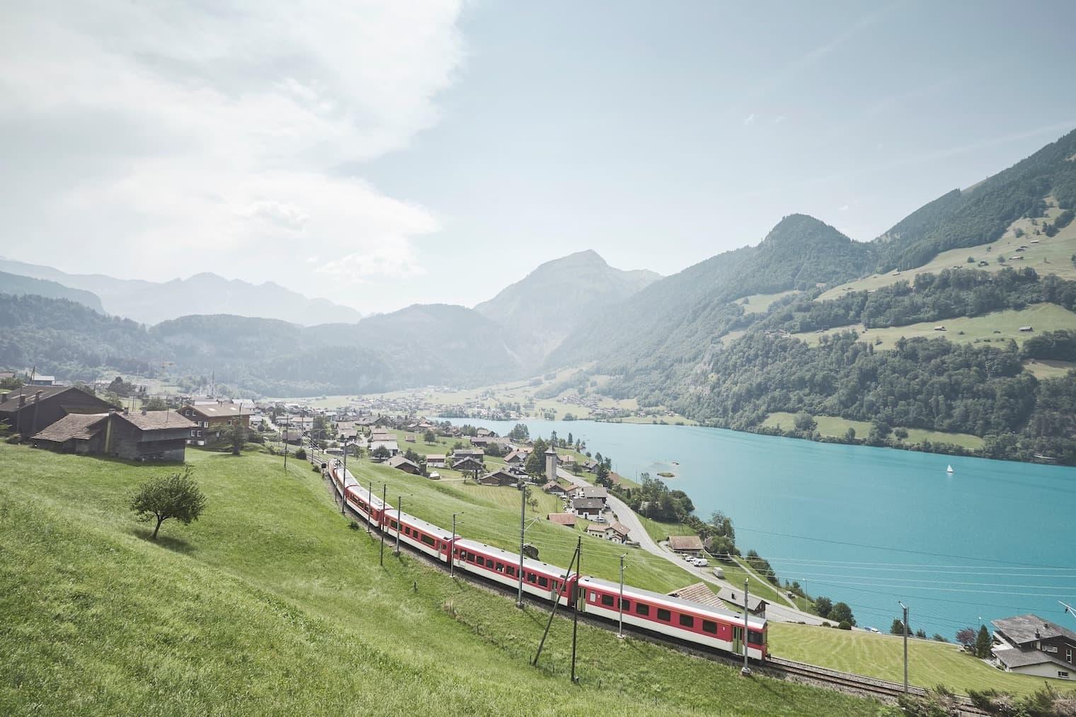 Una ferrovia corre davanti a un panorama rurale costituito da montagne e un lago.