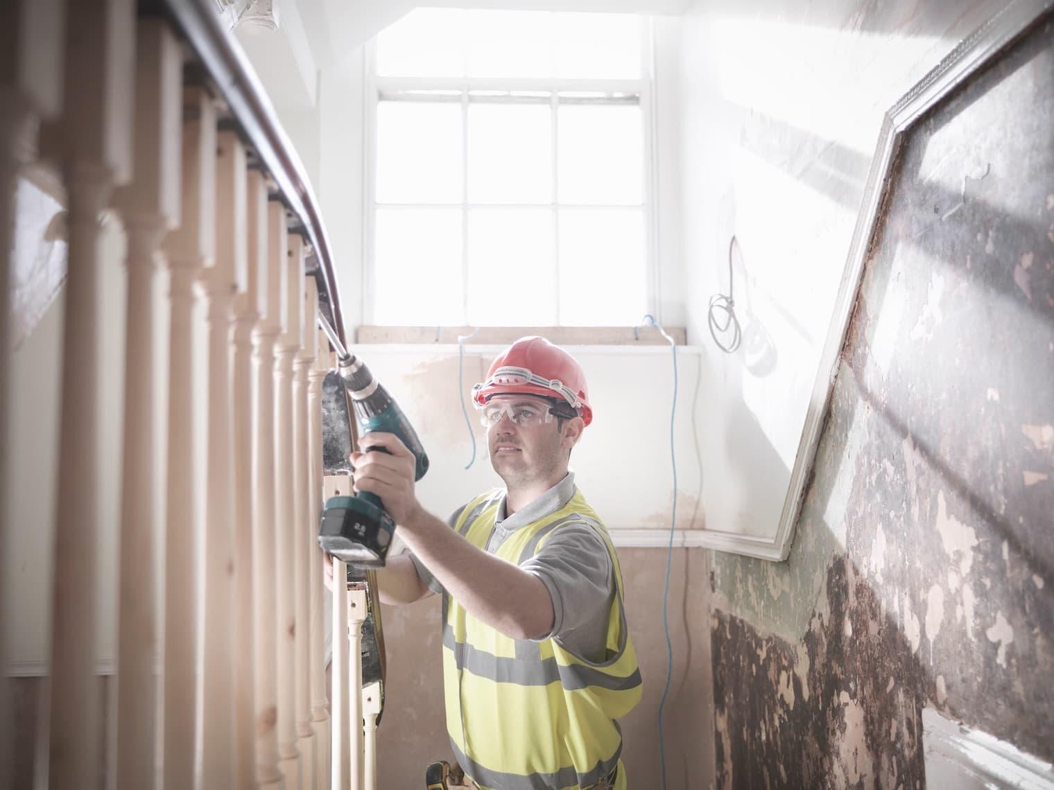 Un homme avec un casque de chantier et un gilet de sécurité dans une cage d'escalier effectue des travaux sur la rampe avec une visseuse sans fil.