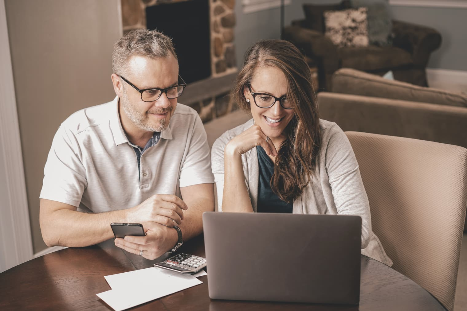 Una coppia seduta al tavolo con calcolatrice, laptop e smartphone.