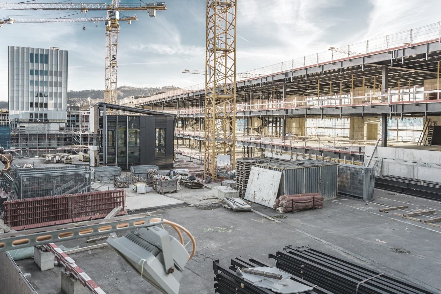 Un gros chantier et un immeuble en arrière-plan.