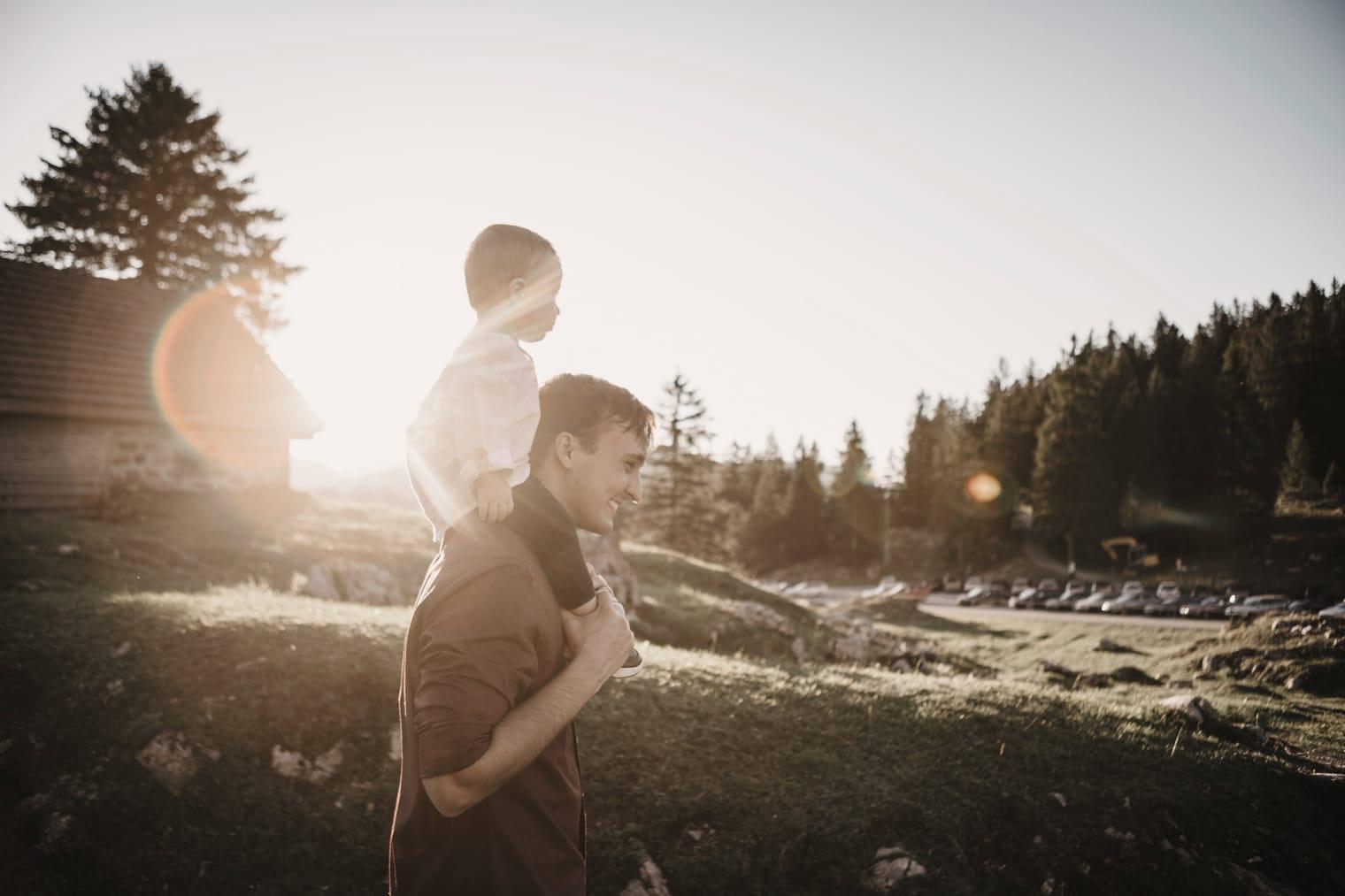 Un uomo porta un bambino piccolo sulle spalle