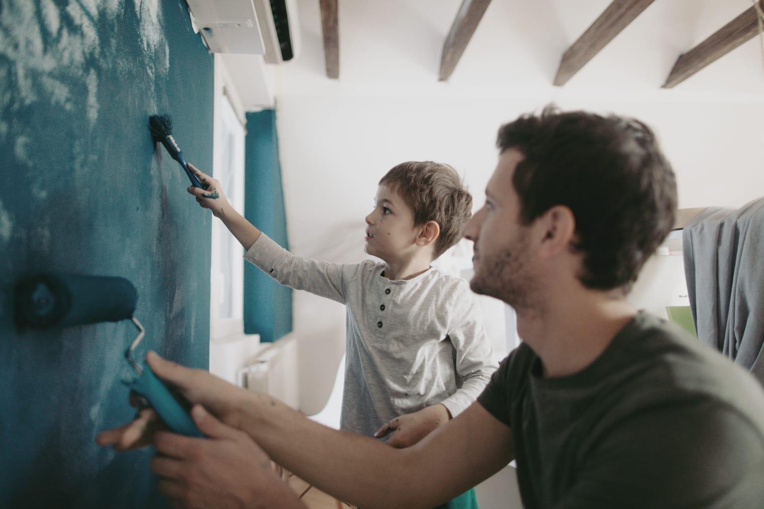 Un père peint les murs avec son fils.