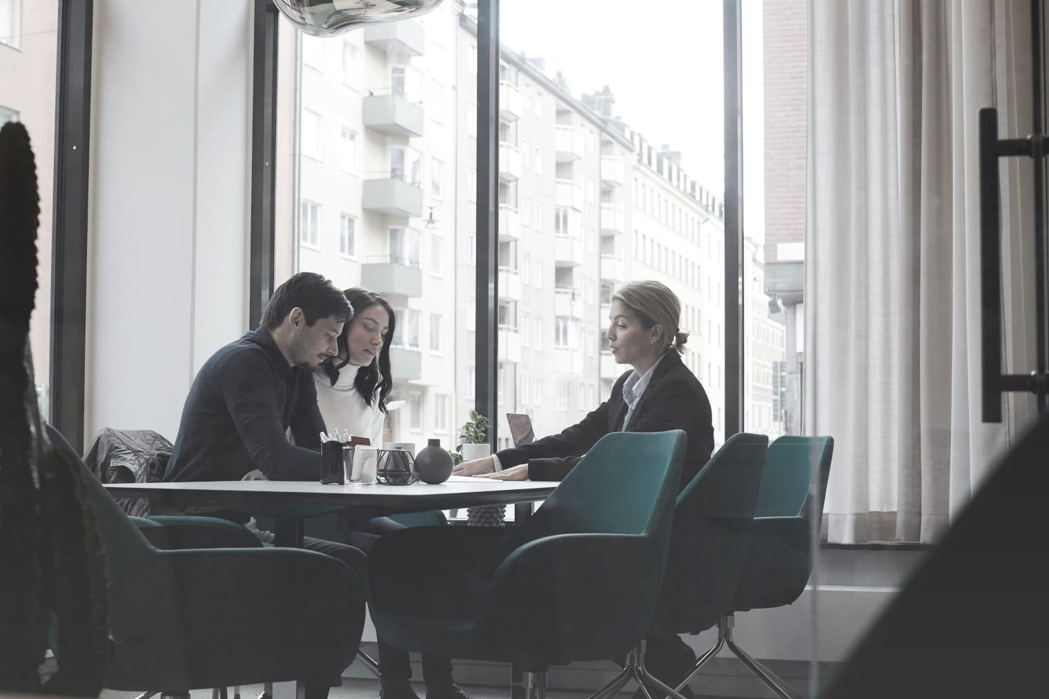 Trois personnes sont assises dans une pièce et consultent des documents