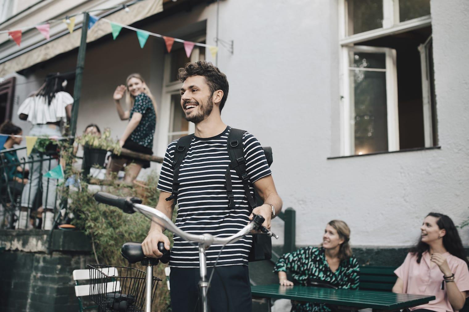 Ein junger Mann hält lächelnd sein Fahrrad. Im Hintergrund sind weitere gut gelaunte Menschen zu erkennen