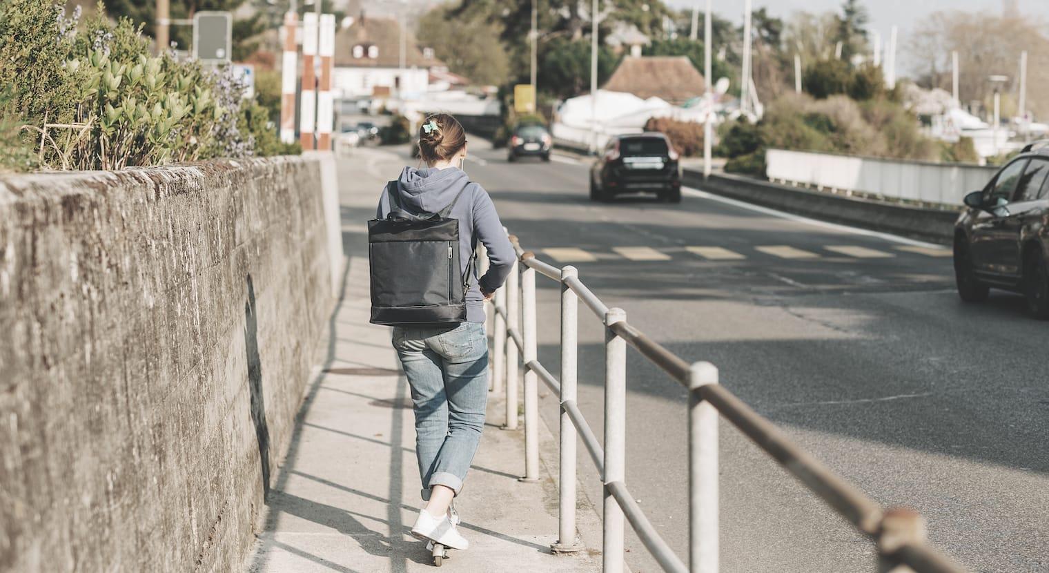 Vista da dietro di una donna che gira su un monopattino lungo una strada.