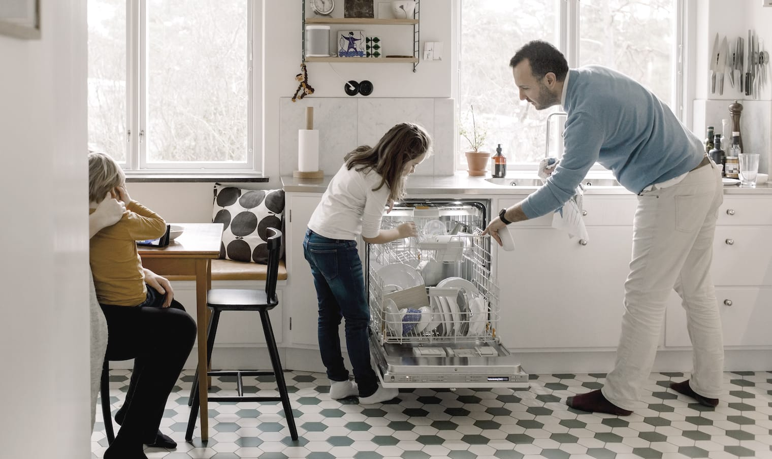 A father loads the dishwasher with his daughter