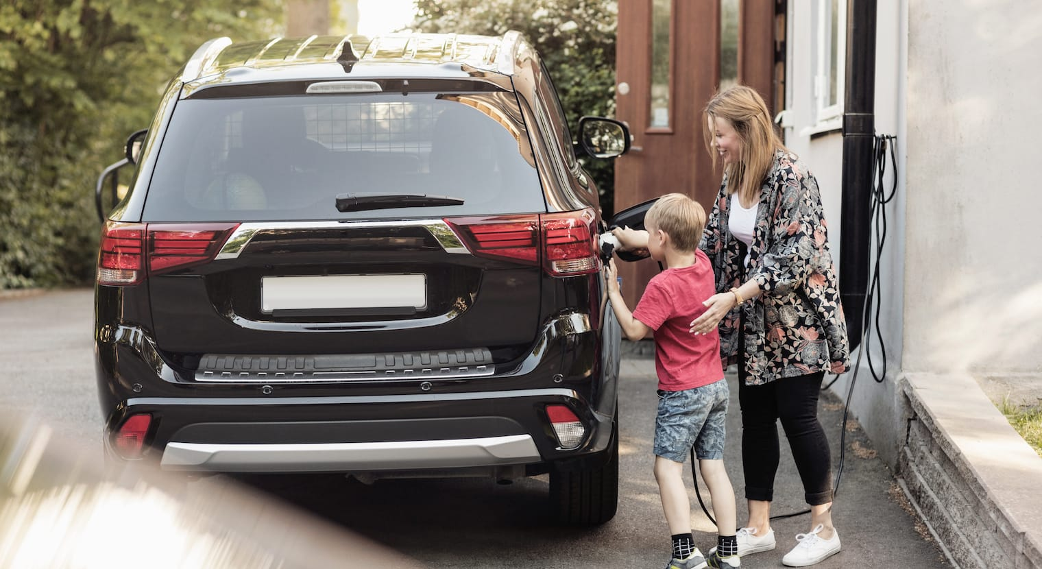A woman and her son charging their electric car